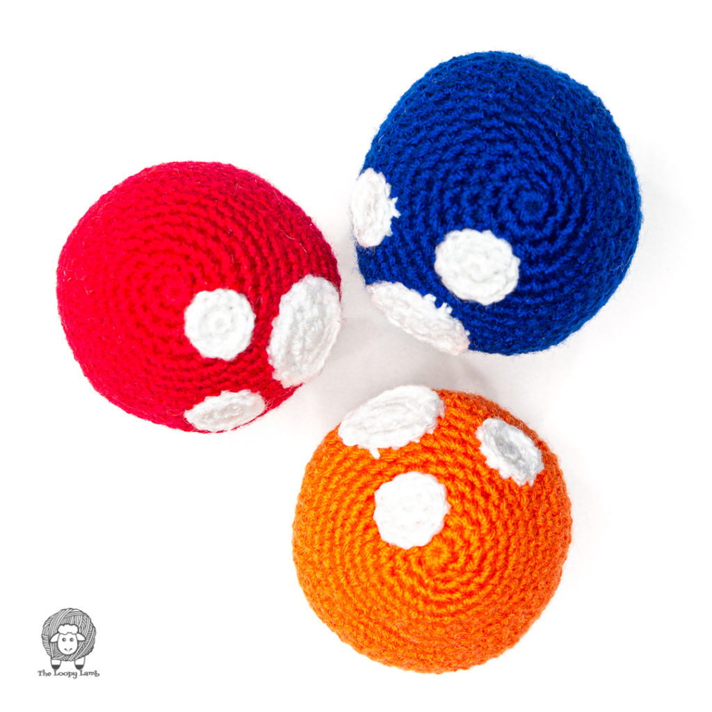 top-view of the amigurumi toadstools in red, blue and orange