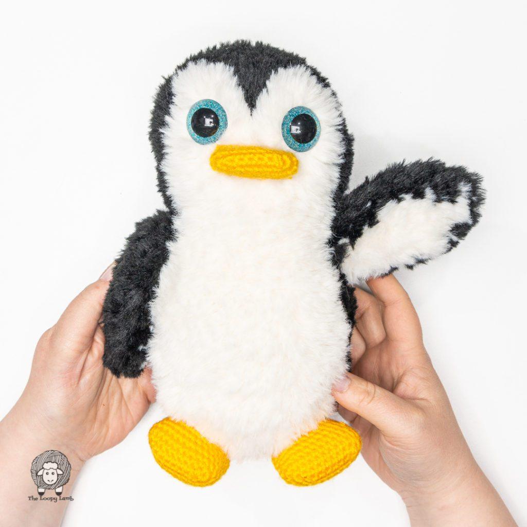 amigurumi penguin made with faux fur yarn waving to the camera