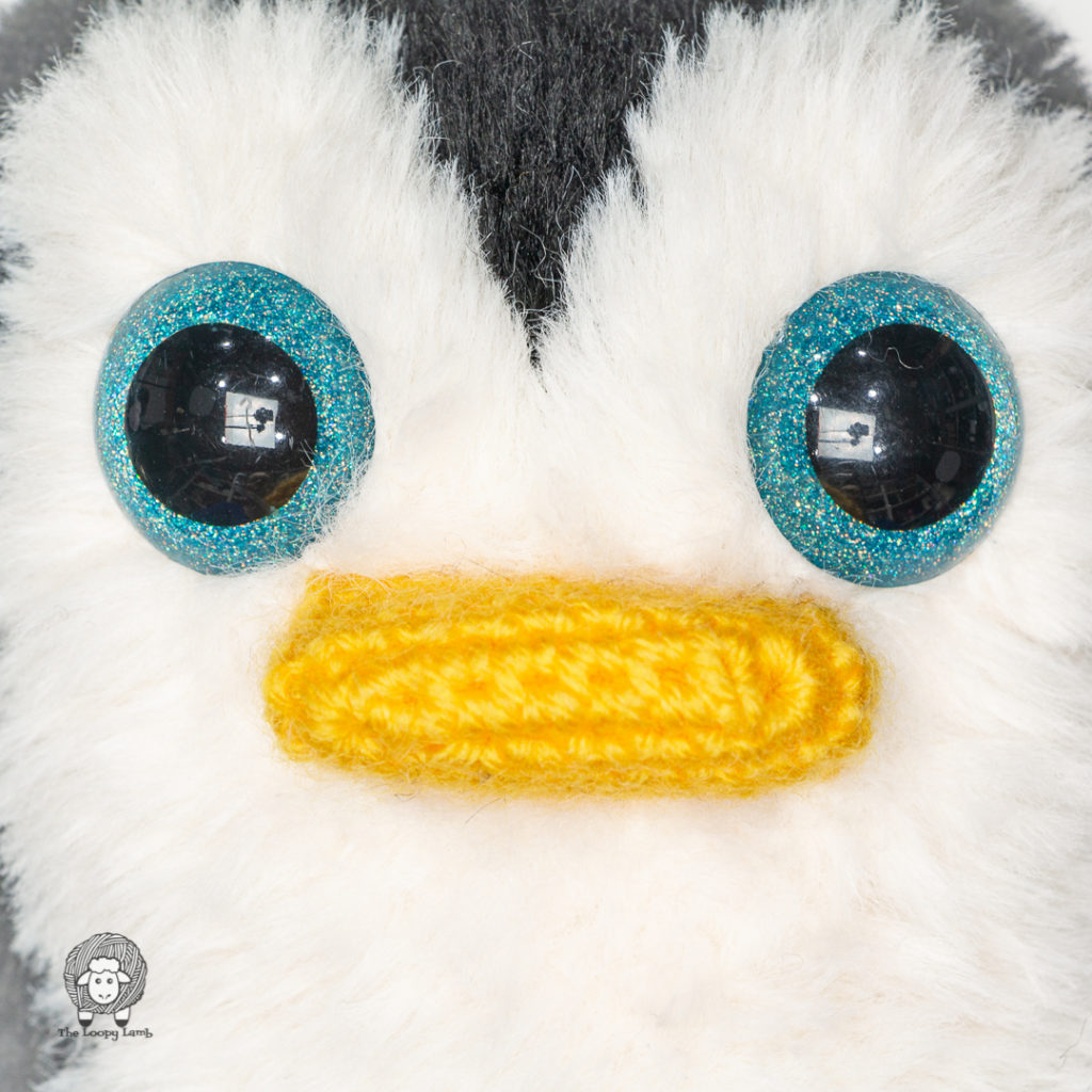 close up image of the face of the penguin made with his free crochet penguin pattern