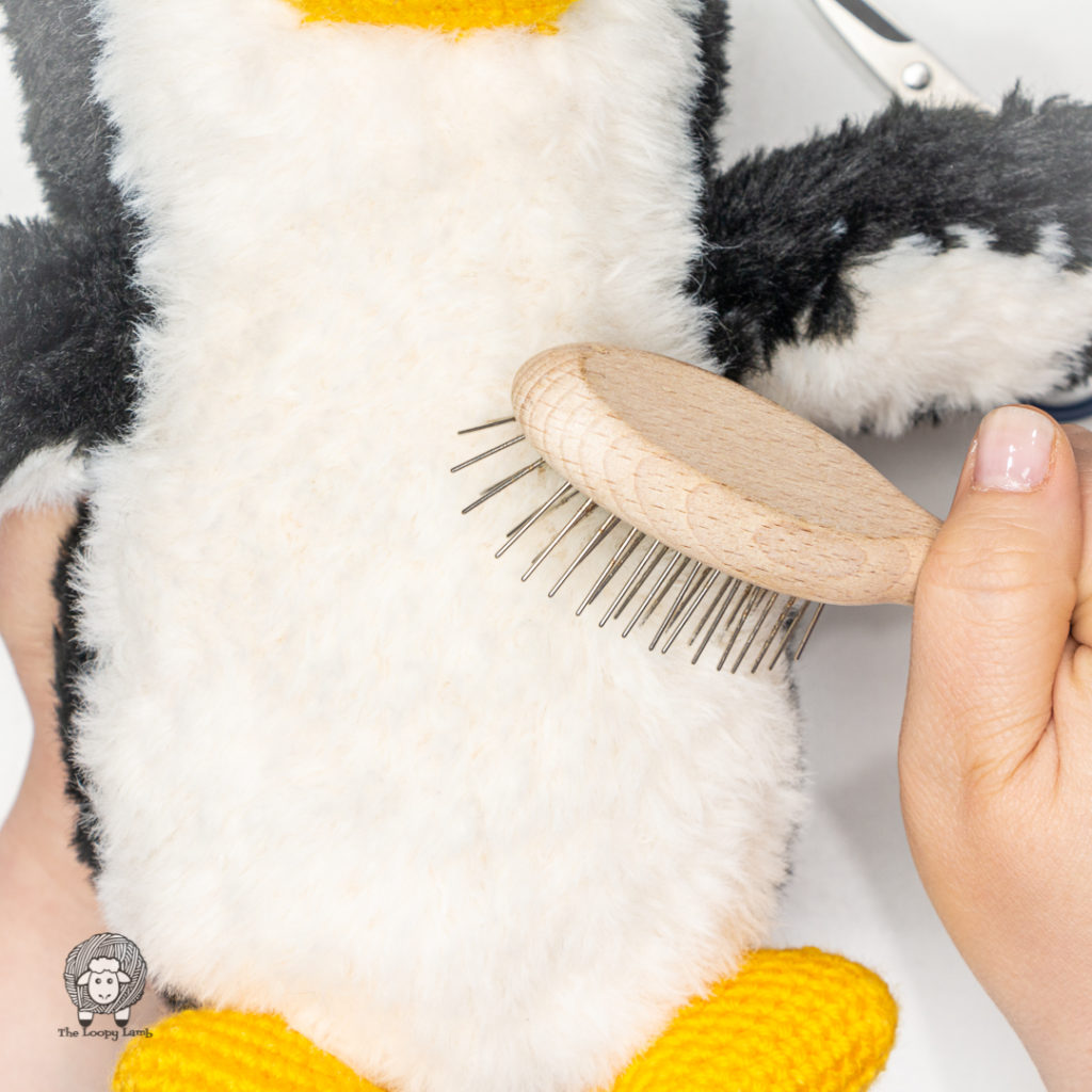 hand brushing out the fur on the amigurumi penguin