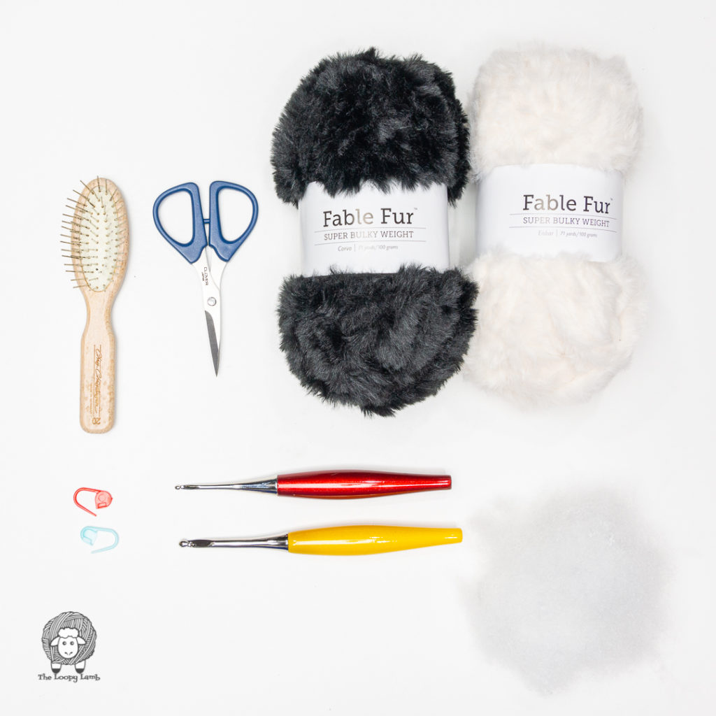 Fable Fur Yarn and Furls Crochet hooks in a flat lay with materials used in this free crochet penguin pattern