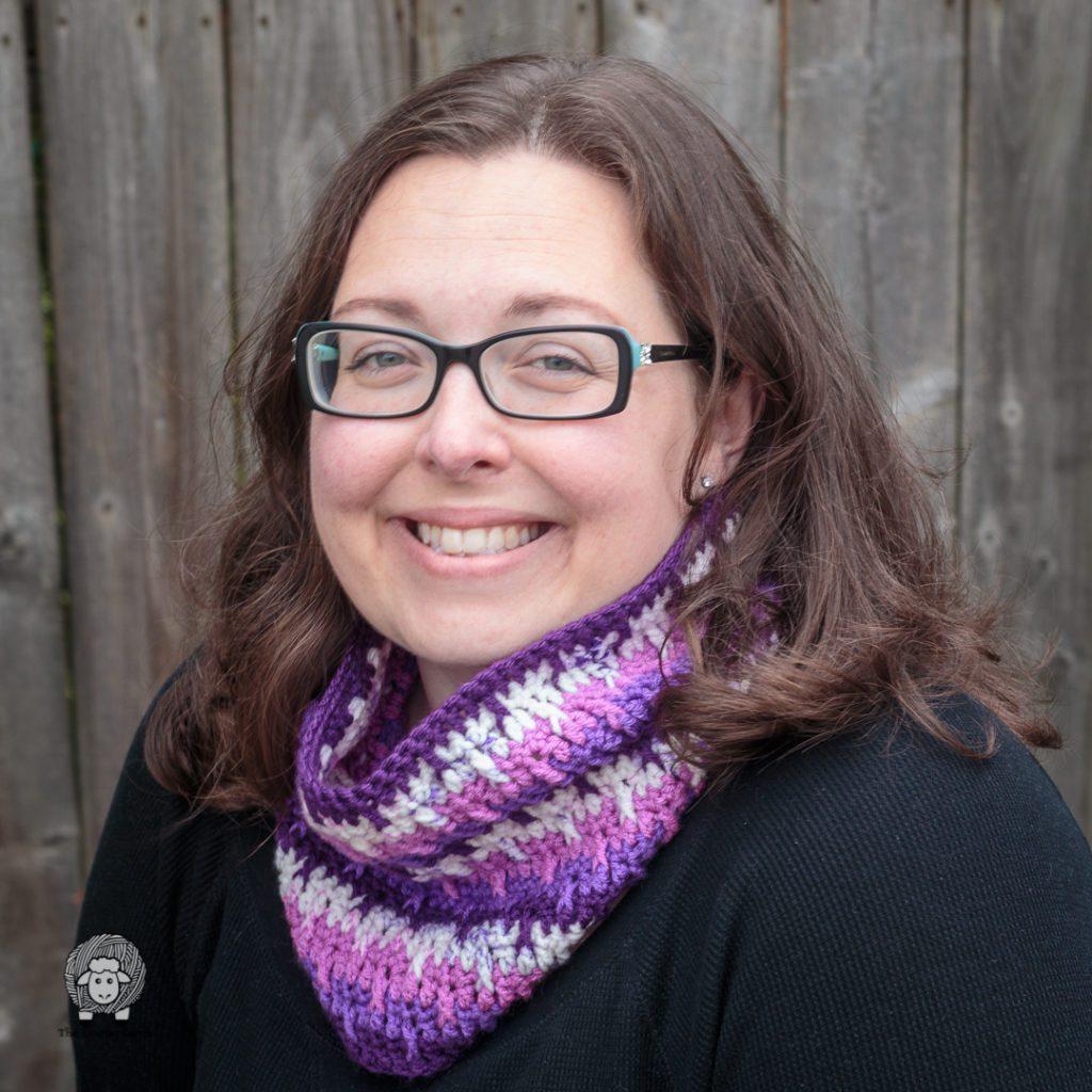 smiling woman modlelling a purple crochet cowl
