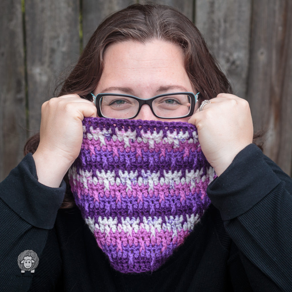 woman peeking over the top of a cowl made with this free pattern for a crochet cowl