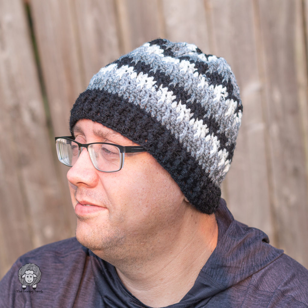 man modelling the shifting posts hat made with this free crochet pattern for a hat