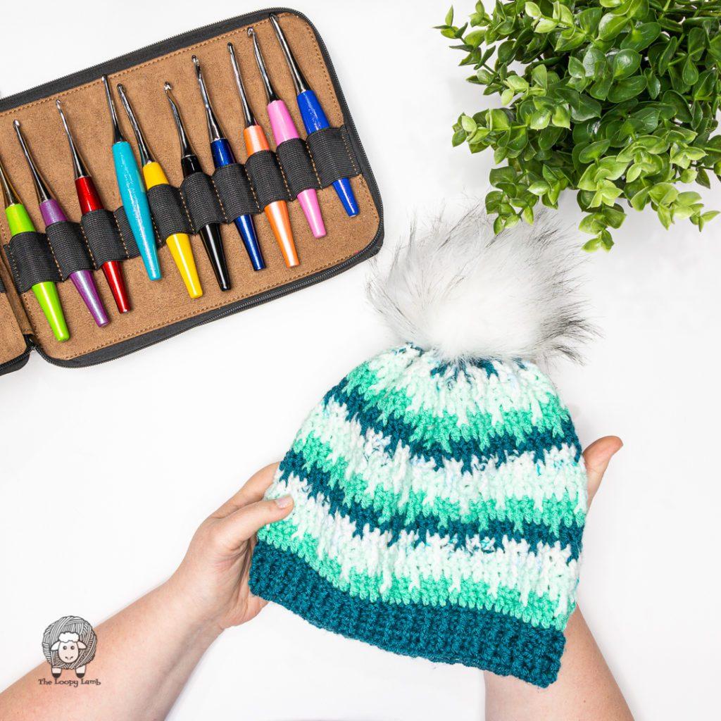 hands holiding the shifting posts crochet beanie with a pom pom
