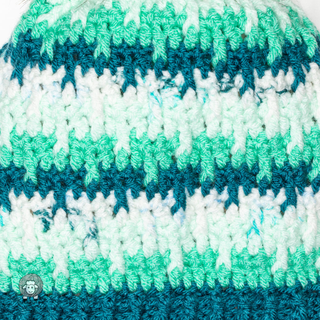 close up of the texture of the shifting posts hat in greens
