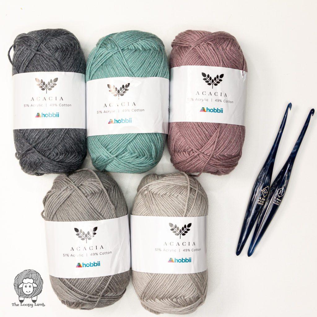 5 balls of Hobbii Acacia next to 2 furls crochet hooks