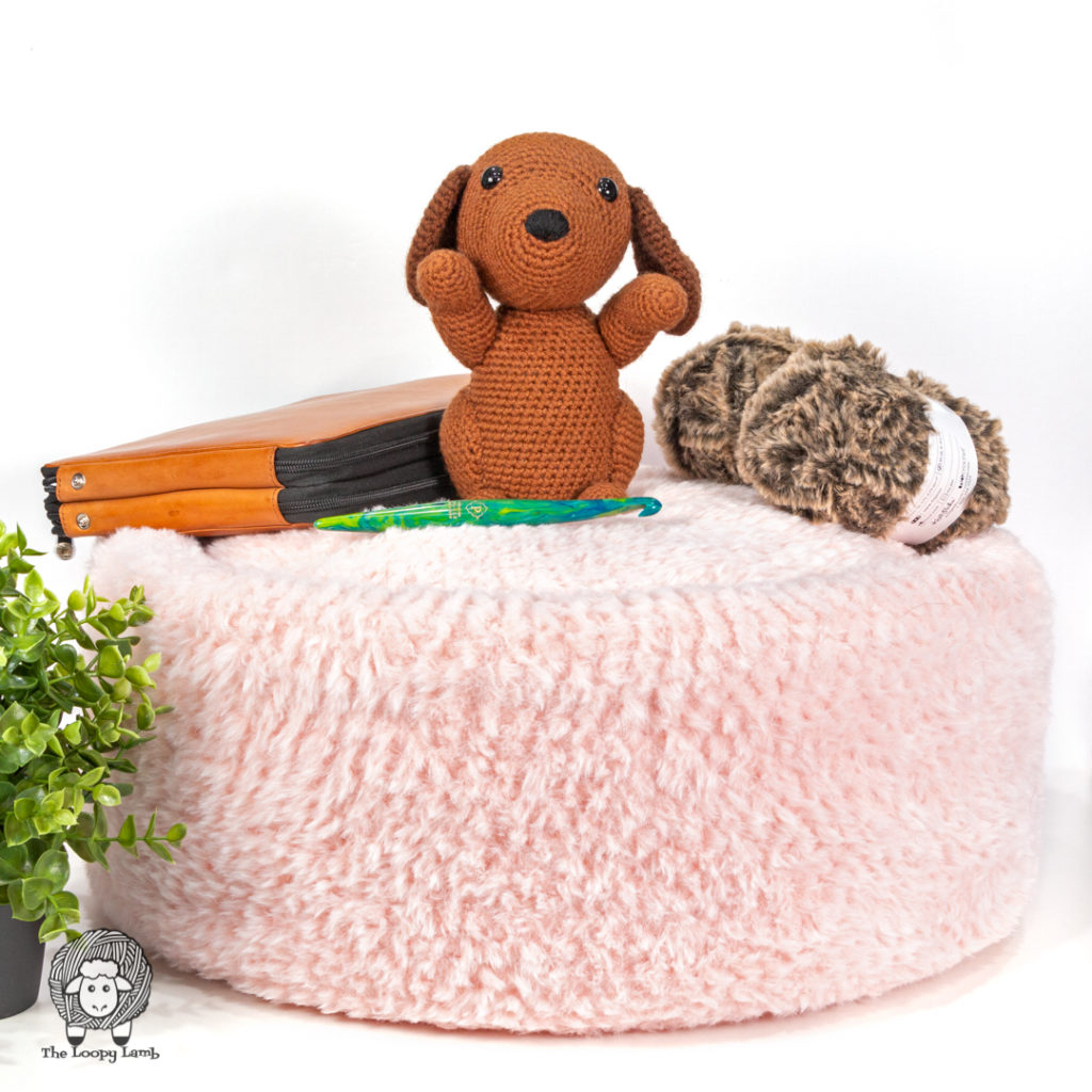 amigurumi dog sitting on top of a faux fur pet bed made with this free crochet pattern