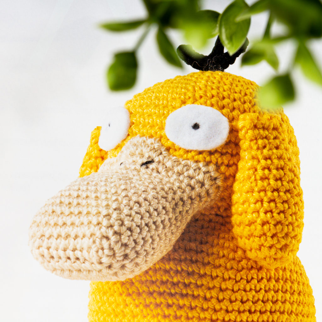 close up image of crochet psyduck © 2021 Pokémon. TM, Ò Nintendo.