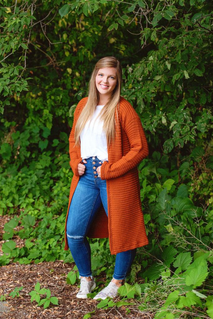 Woman modelling a crochet duster cardigan in copper