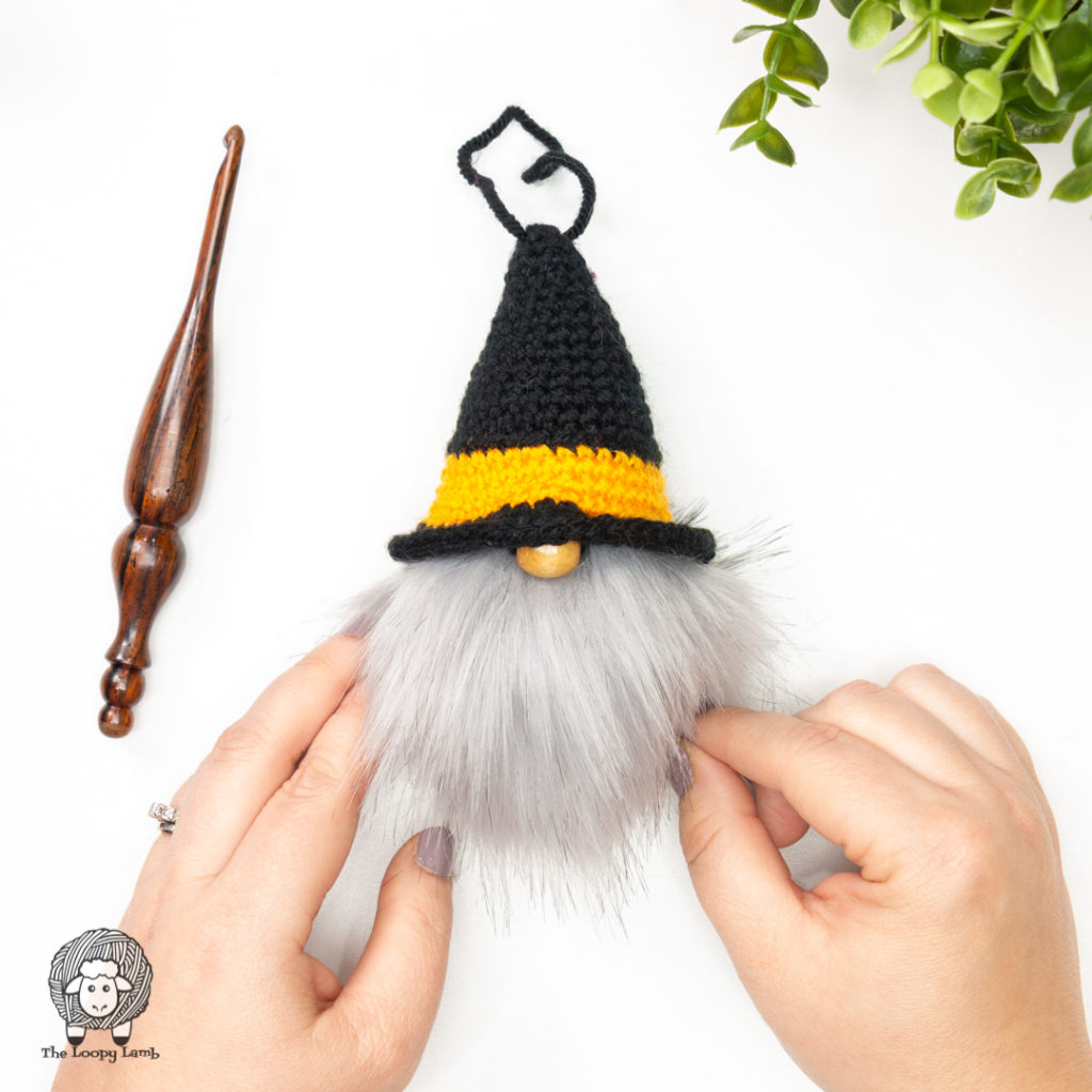 pom pom gnome being held with hands, next to a furls crochet hook