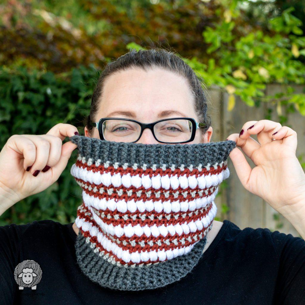 woman hiding her face behind a crochet cowl#wecrochetofficial #wecrochet #stitchandhustle #2021StitchAndHustleBlogHop