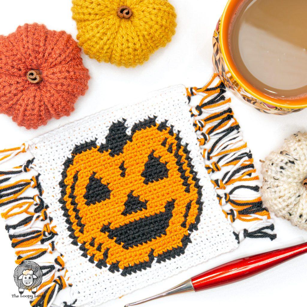 Halloween Jack o' lantern crochet coaster with a furls crochet hook in a flat lay