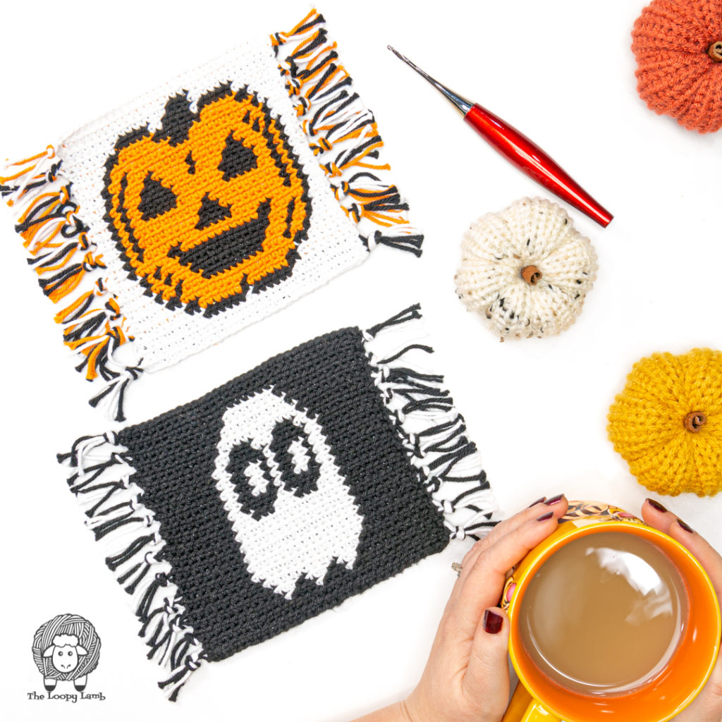 Crochet Halloween Coasters in a flat lay with knit pumpkins and a furls odyssey hook.