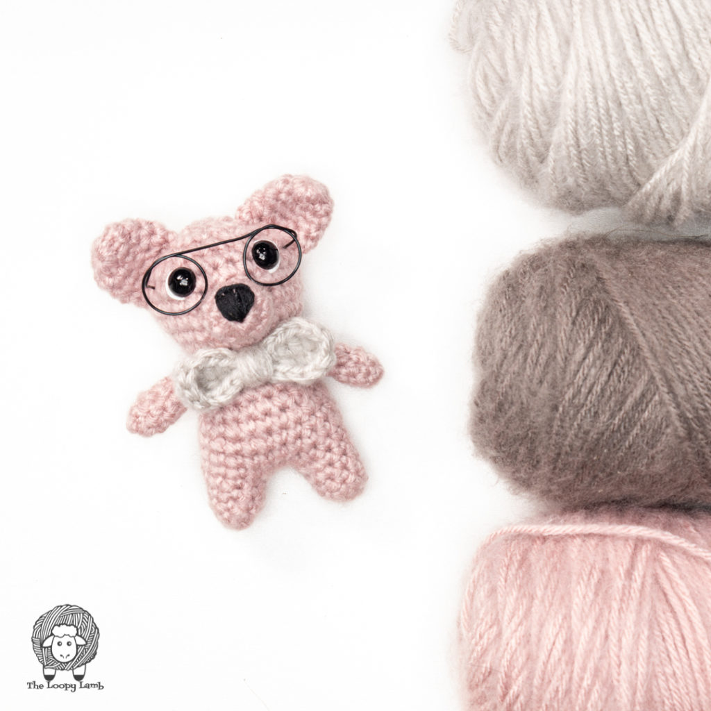 pink amigurumi bear wearing glasses and a bowtie