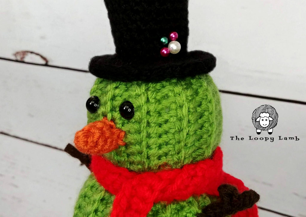 close up image of the face of the crochet cactus snowman made with this free crochet pattern